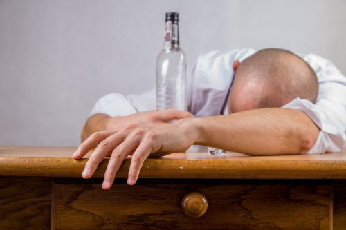 A man sitting slumped over a bar with an empty bottle in one hand.
