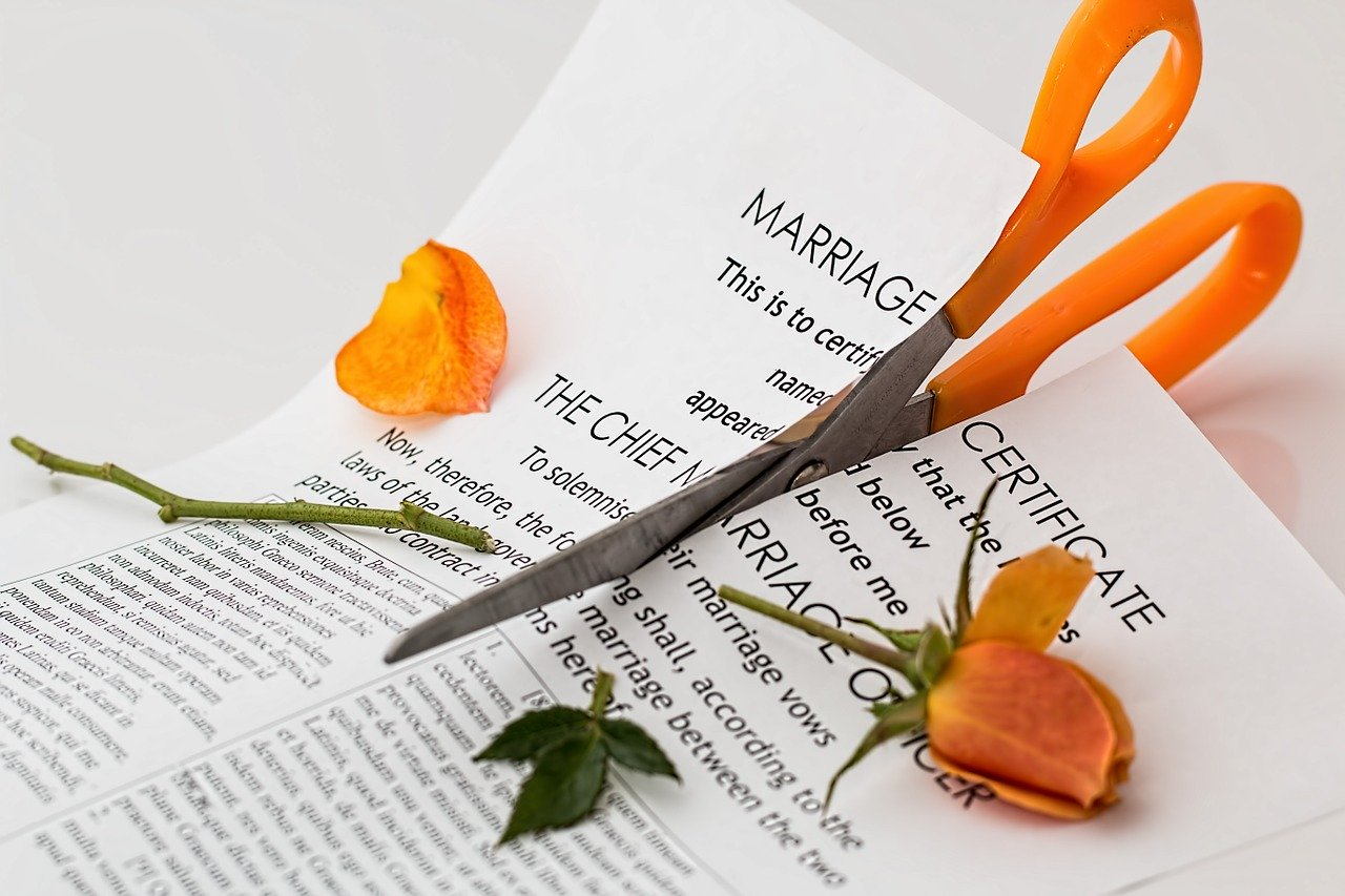 Scissors cutting through a marriage certificate and orange rose
