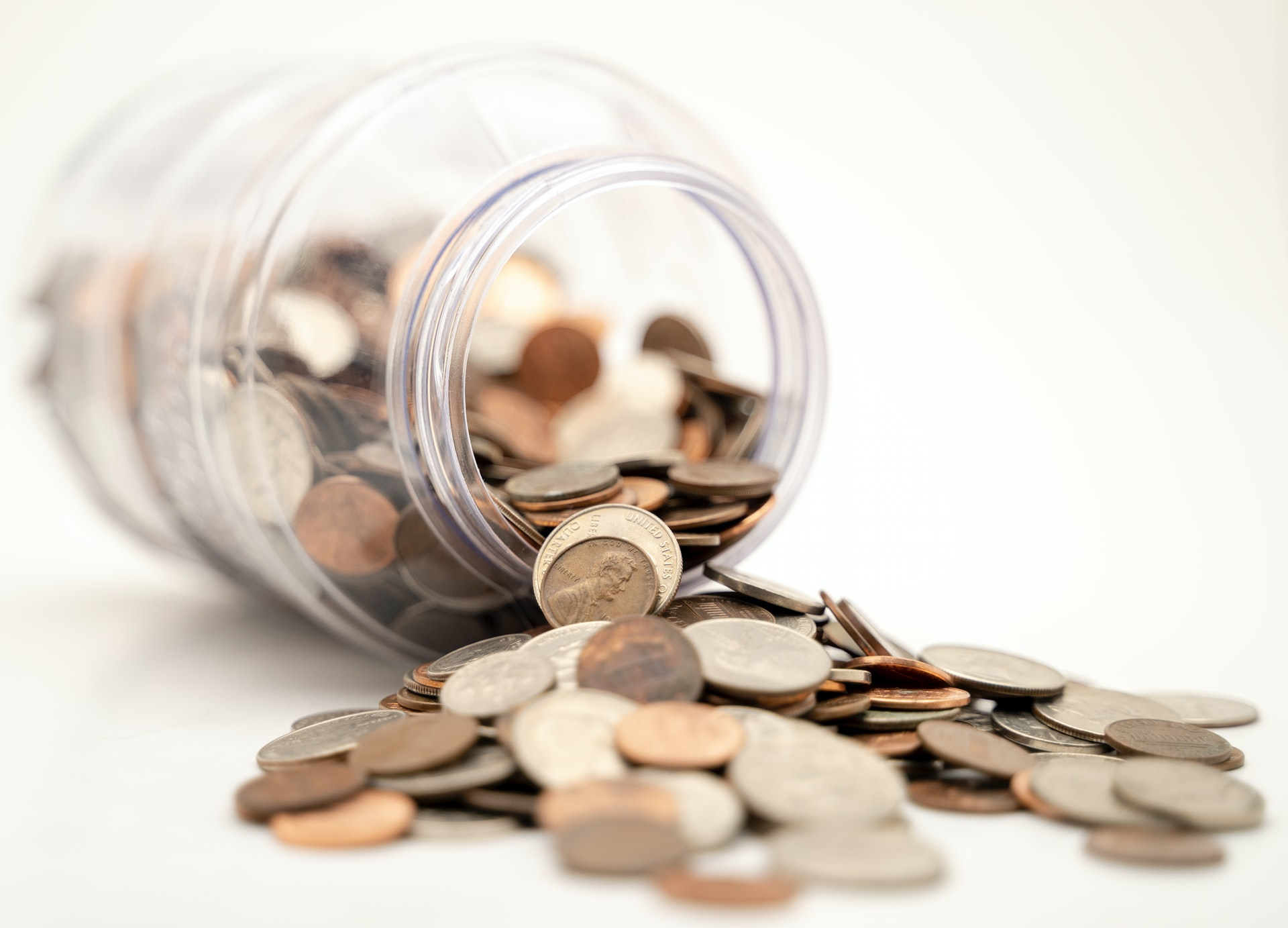 Coins spilling out of a glass jar