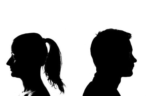 Silhouettes of two people facing away from each other