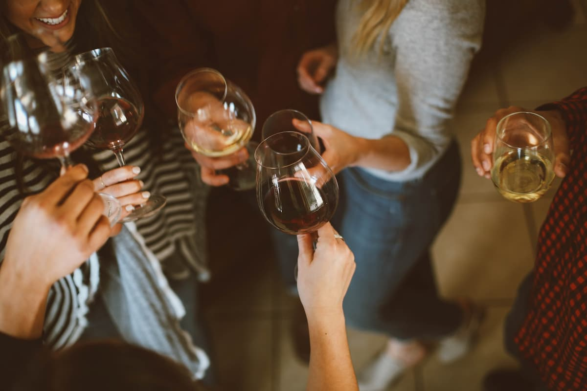 Partiers holding up wine glasses